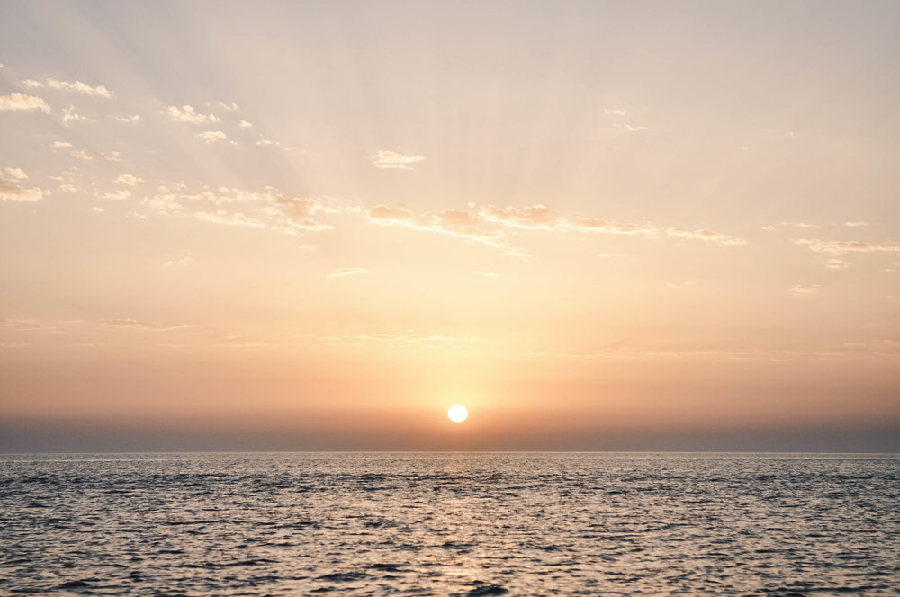 One of the most beautiful sunsets I've ever seen. Taken from a catamaran in Oia,Santorini, Greece