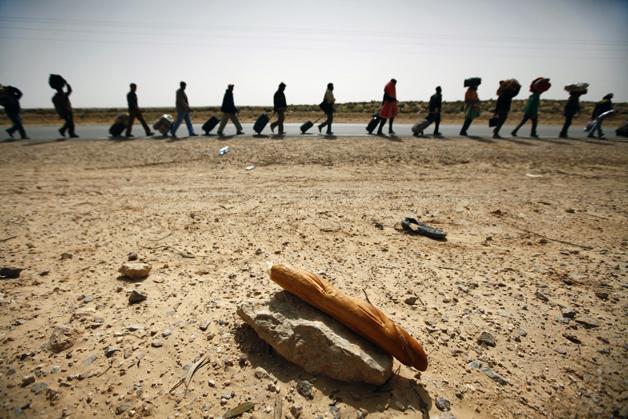 REUTERS/Yannis Behrakis. Refugees crossing the Libyan-Tunisian border.