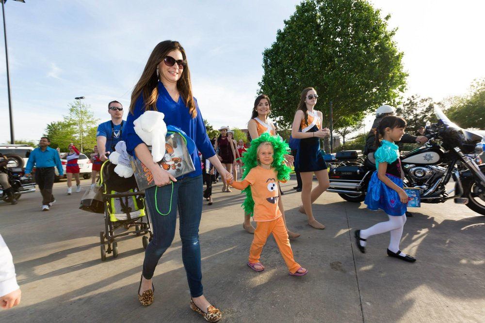 Child and Parent walk in Fort Bend County Arts Festival Storybook Character Parade
