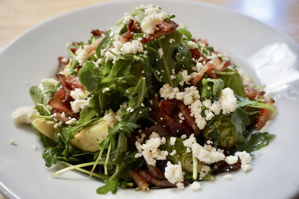Arugula & Brussels Salad - arugula*, roasted brussels sprouts*, carrots*, bacon*, and feta cheese* tossed in a house-made Balsamic Vinaigrette* (sub bacon* for avocado*)Made with fresh and organic* ingredients