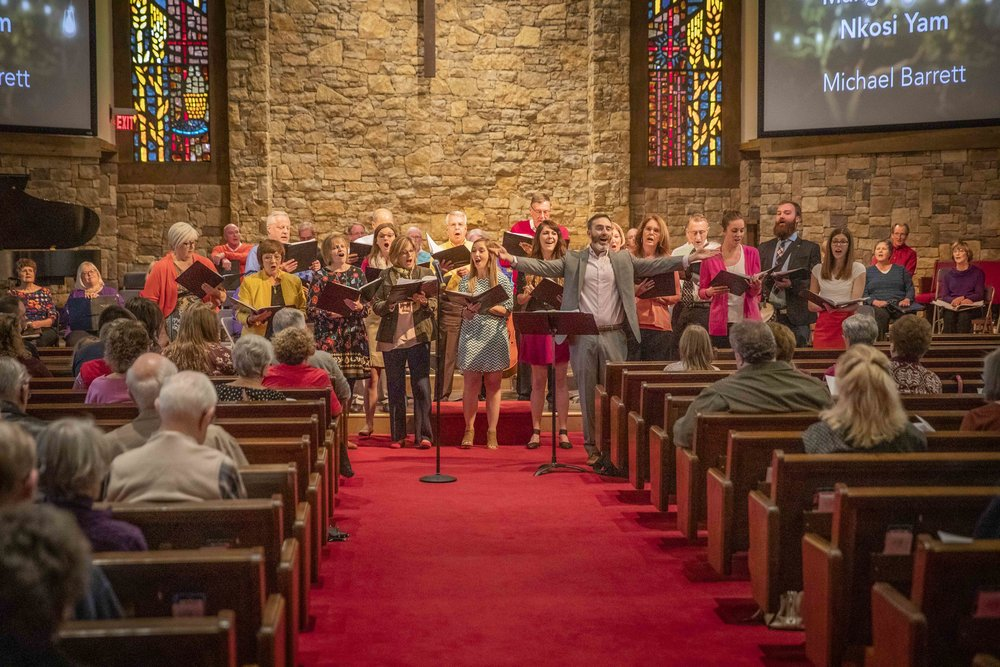 Ryan Main and the choir sing along with the congregation