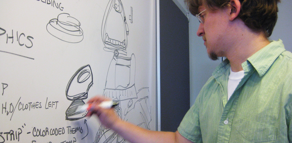 Male designer sketching steam irons on a whiteboard with a black marker