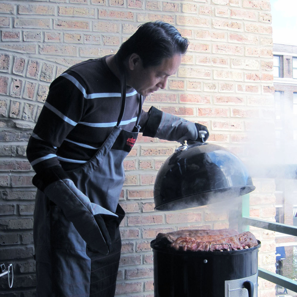 Man grilling ribs on a Weber smoker