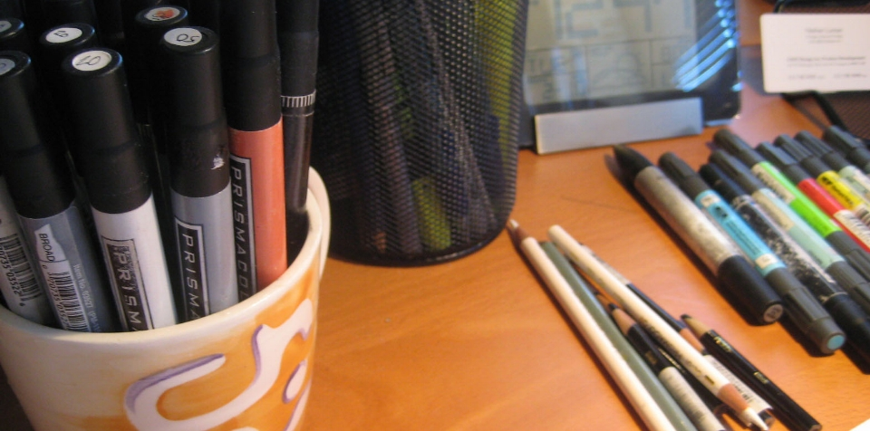 prismacolor markers and colored pencils resting in a CHOi Design coffee mug and on the desk