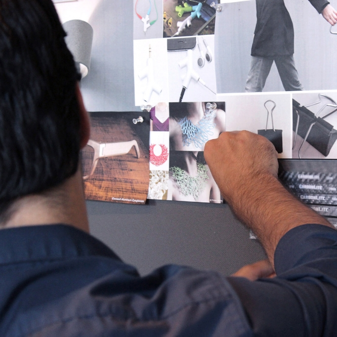 Designer pinning image on inspiration wall at CHOi Design