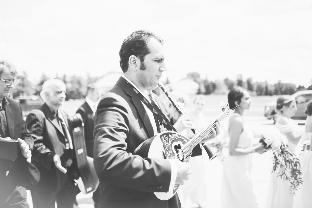 The bride was escorted by both her parents, bridal party, family and a Greek band. -