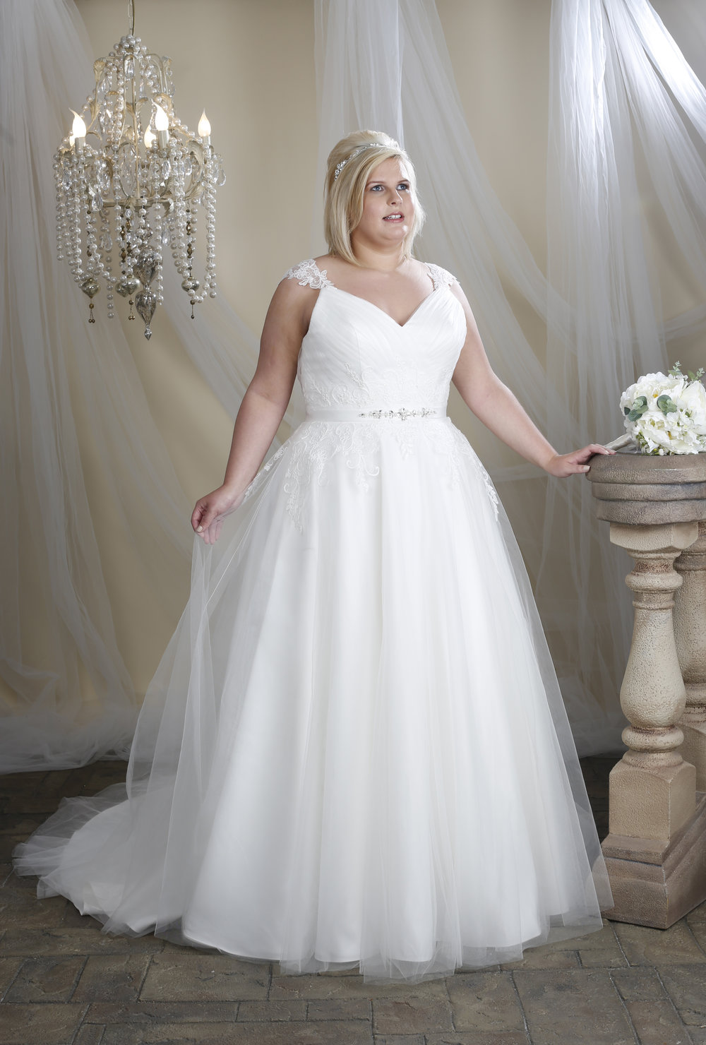 A curvy model wearing a plus size Hilary Morgan wedding dress