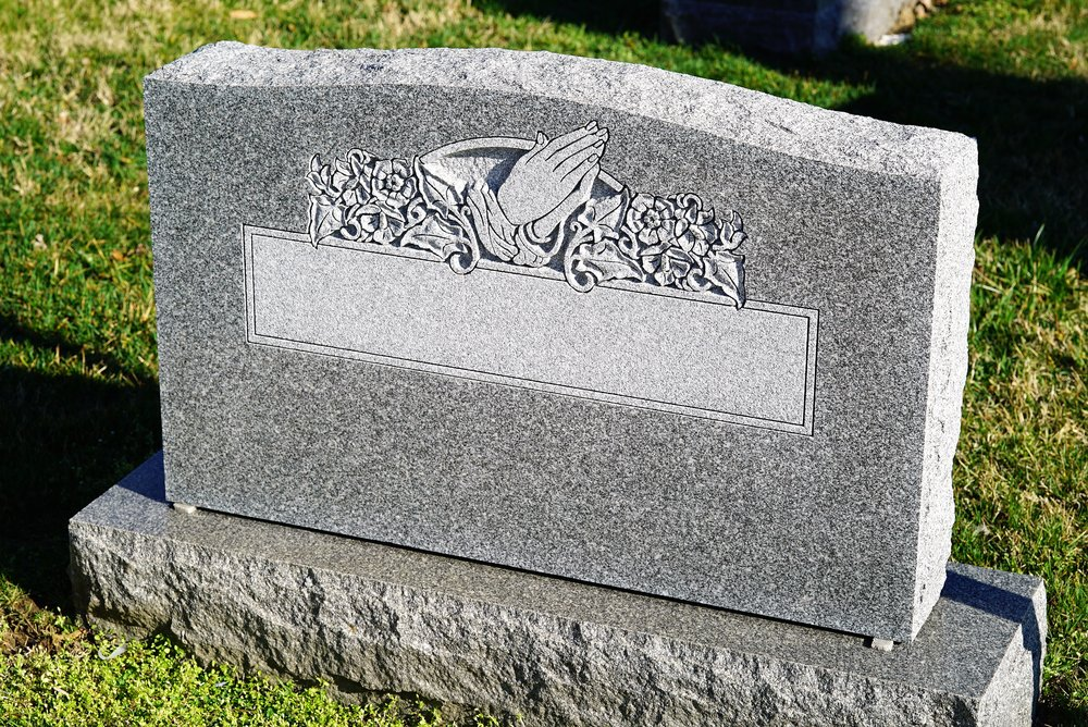 Photo of a blank headstone with a carving and a panel, ready for names and dates to be sandblasted on to it.