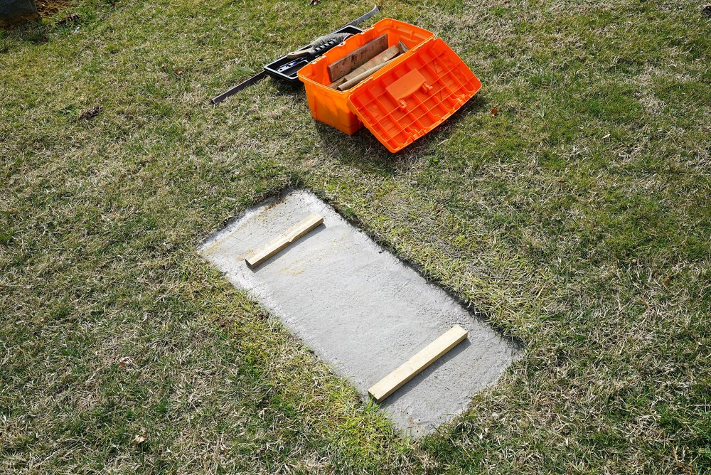 """Photo of a foundation at a grave. The headstone rests on top of this.  (The wood is temporary. It is part of a stone-setter's """"tricks-of-the trade."""")"""