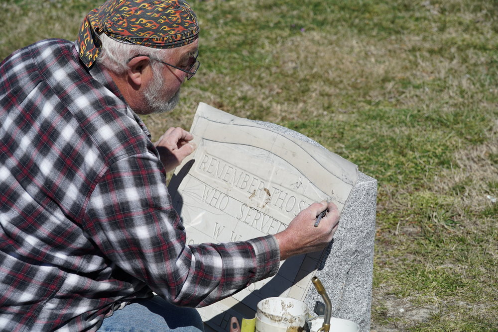 An inscription craftsman is preparing the stencil for a World War 1 monument. Next comes sandblasting.