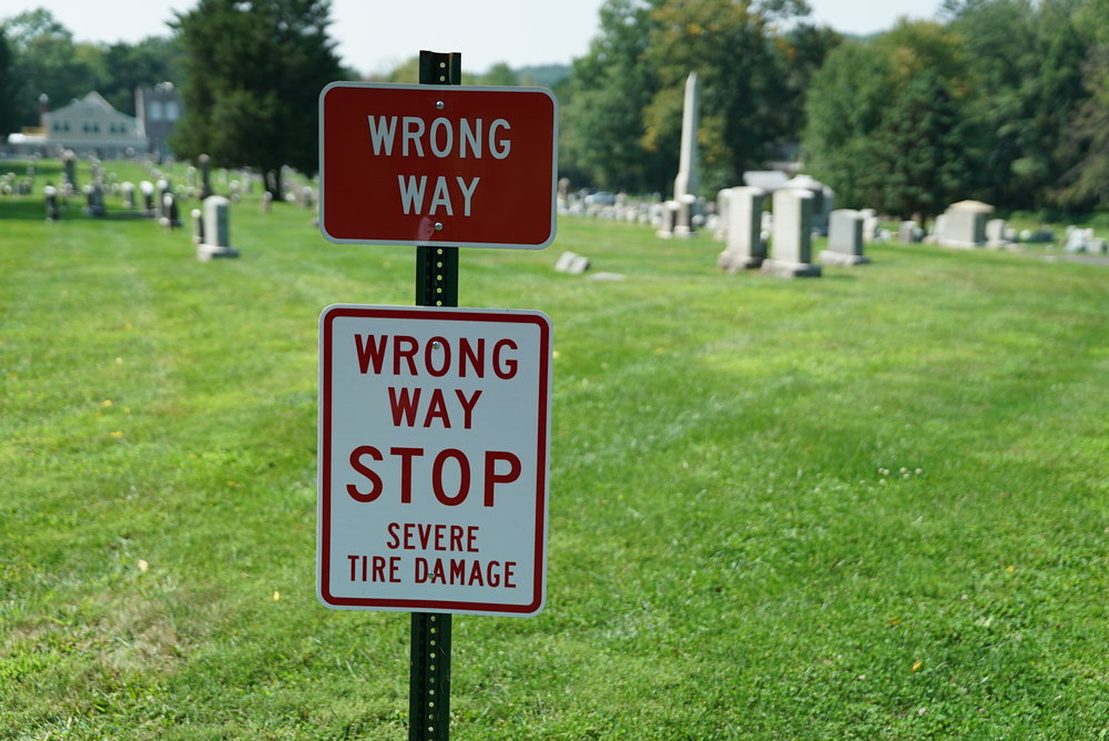 They so much don't want visitors going the wrong way down this driveway that they put this sign in. As of September 2017, this sign was a big lie. I walked the whole driveway. There is nothing there that will cause severe tire damage. Union Cemetery of Whitemarsh at Saint Miriam. Flourtown, Pennsylvania.