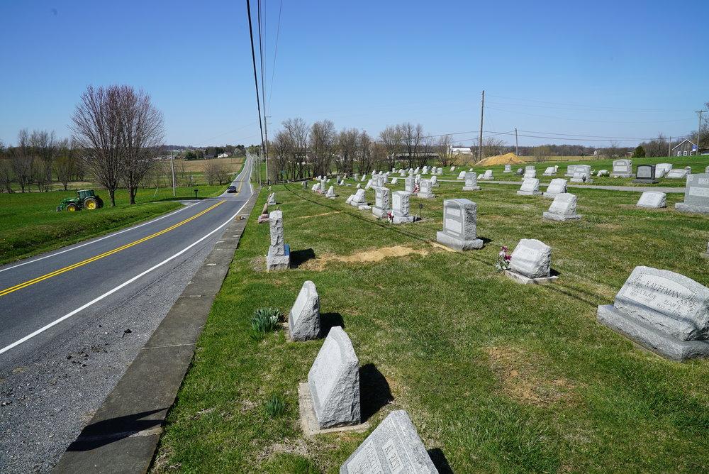 A farm tractor in the distance. Maple Grove Mennonite Church Cemetery. Atglen, Pennsylvania.