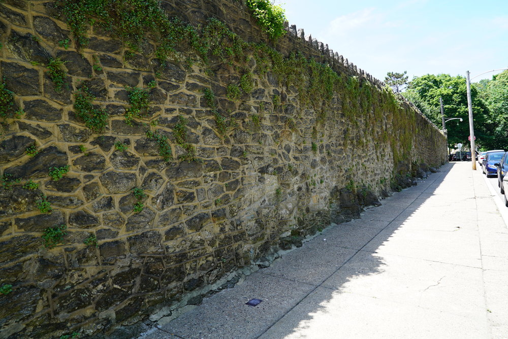 A high wall blocks the view of the cemetery. St. John The Baptist Church Cemetery. Philadelphia, Pennsylvania.