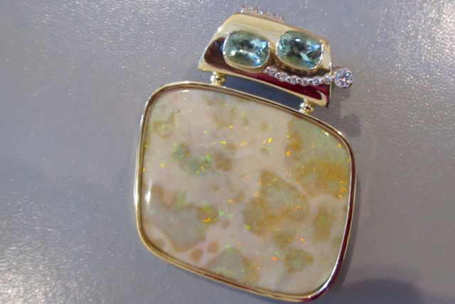 Two-sided pendant. Side B: 18k gold, bezel set Andamooka opal that has been polished front and back. Set with 2 green tourmaline and 2 diamonds.