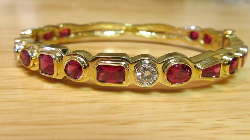 18k yellow gold natural ruby cuff bracelet with 3- 1/3 ct. round diamonds. 16 total natural rubies, approximately .5 ct. each