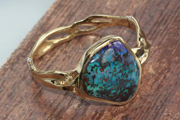 Freedom - 3.5 oz. of 18k yellow gold in a sculpted and hinged bracelet set with a 57 ct. opal