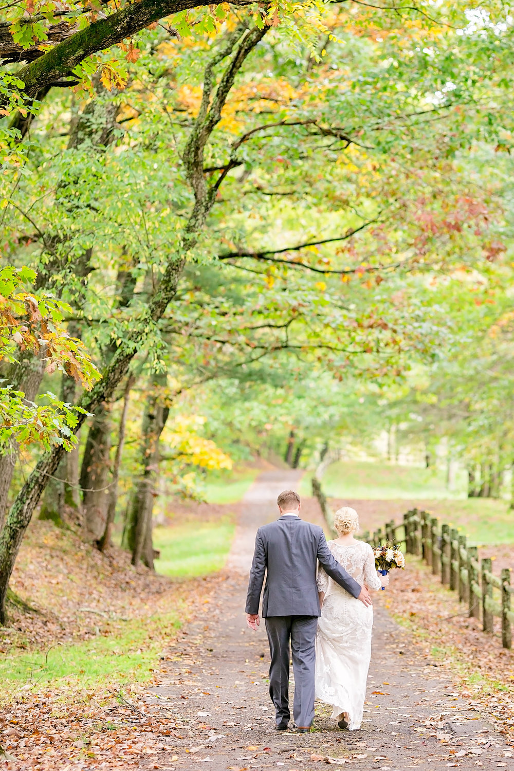 Wedding couple walking on tree-lined path