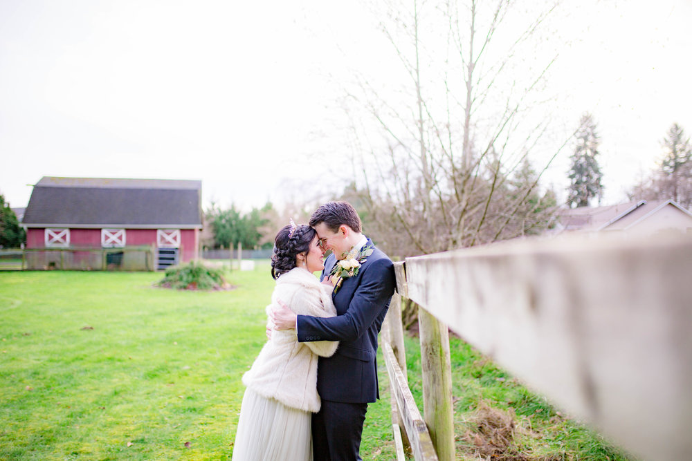 Bride and groom against fence
