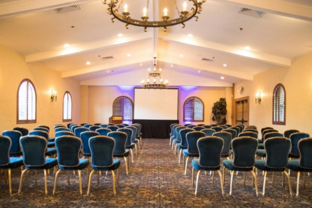 conference room classroom set-up screen presentation lectern uplighting chandeliers blue and gold chairs learning environment