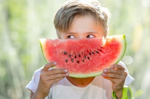 Funny kid eating watermelon outdoors in summer park focus on eyes.jpg