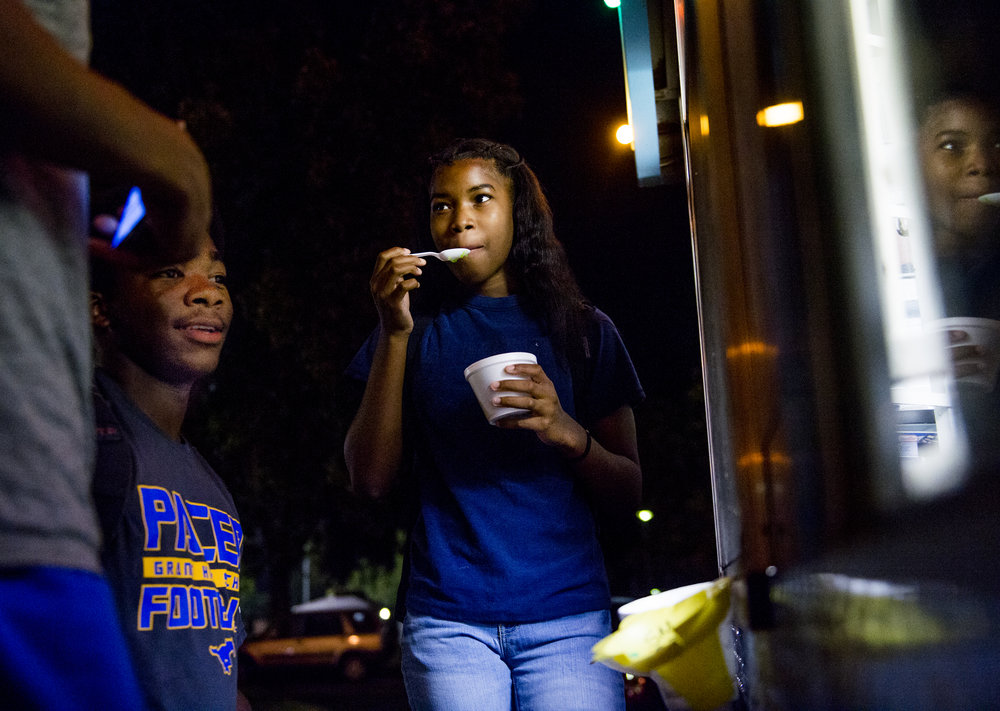Arionna Cooks, 13, right, Robert Harris, 16, and Adrian Cooks, 16, buy shaved ice during the Nightlife Turned Right event at the Robertson Community Center, in Sacramento, Calif. The three day weekly event offers families and children a safe space to play and take various classes during the summer. Neighborhood events have been started throughout Sacramento to bring the community together and keep children away from violence.