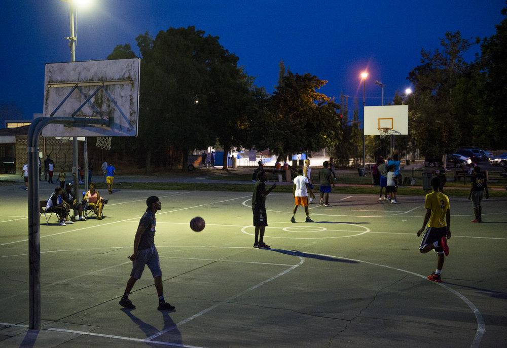 Teenagers play basketball during the Nightlife Turned Right event at the Robertson Community Center, in Sacramento, Calif. The three day weekly event offers families and children a safe space to play and take various classes during the summer. Neighborhood events have been started throughout Sacramento to bring the community together and keep children away from violence.