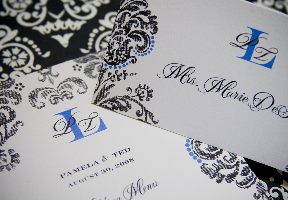 Monogrammed menu and escort card flat printed on felt weave paper in cornflower blue and black ink.