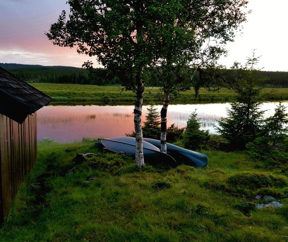 """Kanoene """"Elvegris"""" og """"Åstapurka"""" ligger ved dette naustet 3.7km sør for Øvre Åstbru på samme side av elva som bommen."""