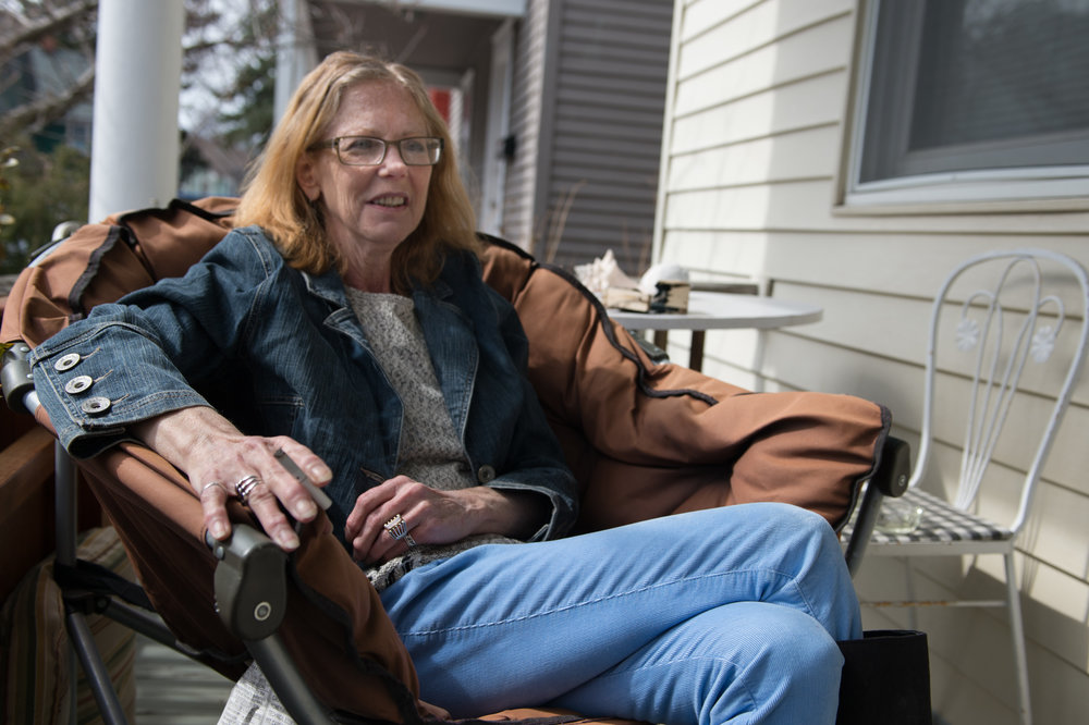 Carol Heveron laughs as she tells a story while sitting on her porch at her house in Rochester, N.Y., Friday, April 3, 2015.