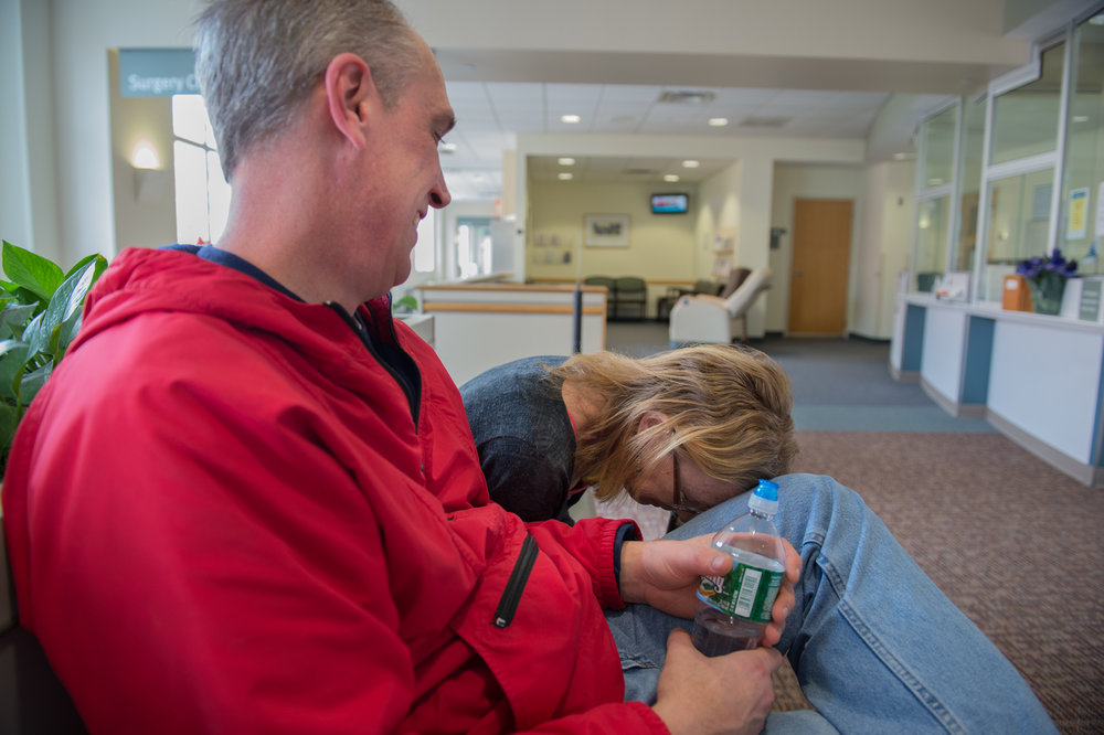 "Carol places her head on her friend Erik Lacelle's knee after having a tube removed from her lungs at Strong Memorial Hospital in Rochester on Thursday, April 2, 2015. ""Erik's a good guy,"" she said. ""Sometimes he comes over on the weekends and we have doughnuts."""