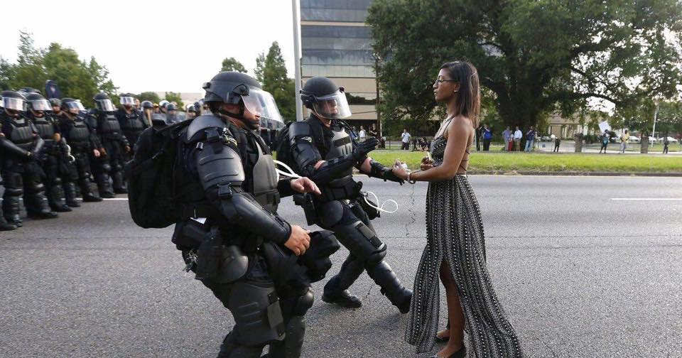 (protester standing up to police in New Orleans).