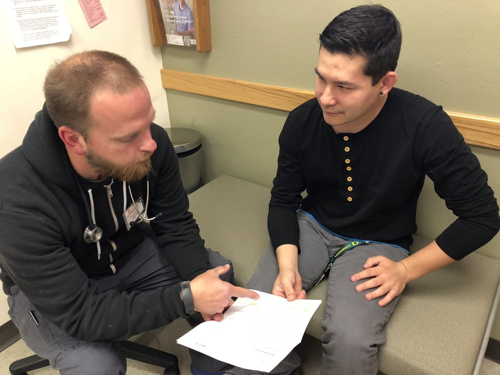Adam White, RN, reviews information about anaphylaxis with Brandon Nakamura, a One Community Health patient.