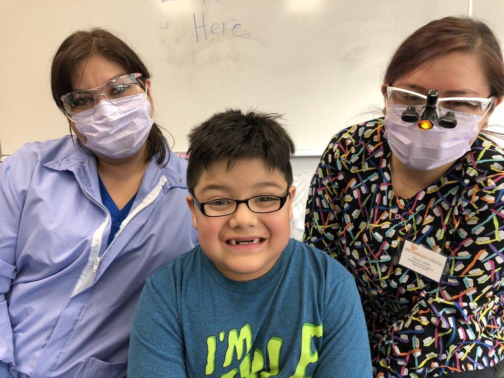 El estudiante de Segundo grado, Nico Ochoa de la escuela primaria Mid Valley se cienta en medio de dos miembros del equipo dental del programa selladores de One Community (de izquierda a derecha): Cynthia Valdovinos, EFDAH, y Sylvianna Marquez, RDH.