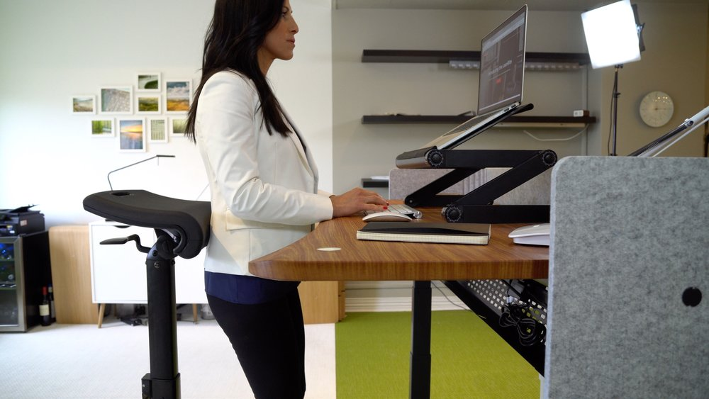 The LeanRite adjusts easily to support the body in numerous working postures sit-to-stand. Here, a 'lumbar lean' posture is demonstrated with lumbar support providing relief to the body when working standing up.