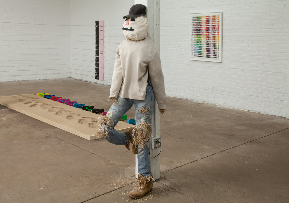 """Automated Promotion or Dire Warning? This Scarecrow Playing a Live Feed of A Conversation Taking Place Inside at Full Volume Outdoors Will Get the Business You Place it In Front of Whatever Customers it Deserves    72""""x14""""x18""""    clothing straw wood substructure speakers    2017"""