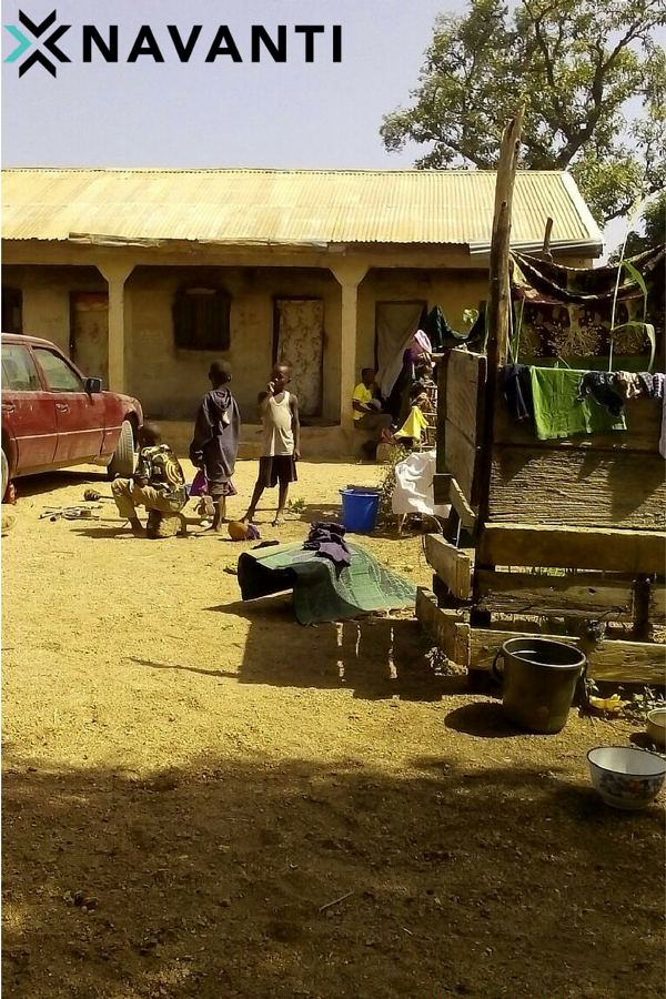 Youth in front of household in Vi Village, Michika LGA