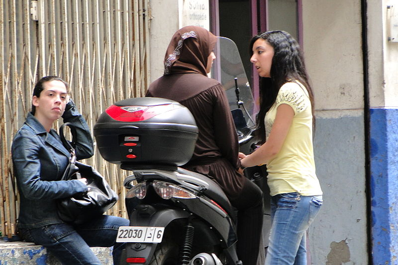 Trio of girls with a motorbike. Source: Wikimedia Commons