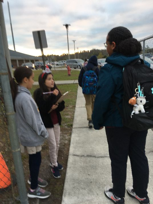 Pride Student Ambassadors checking in classmates walking to school.