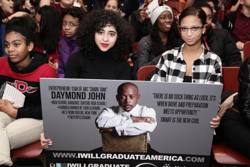 Enthusiastic students pose with Daymond John poster.