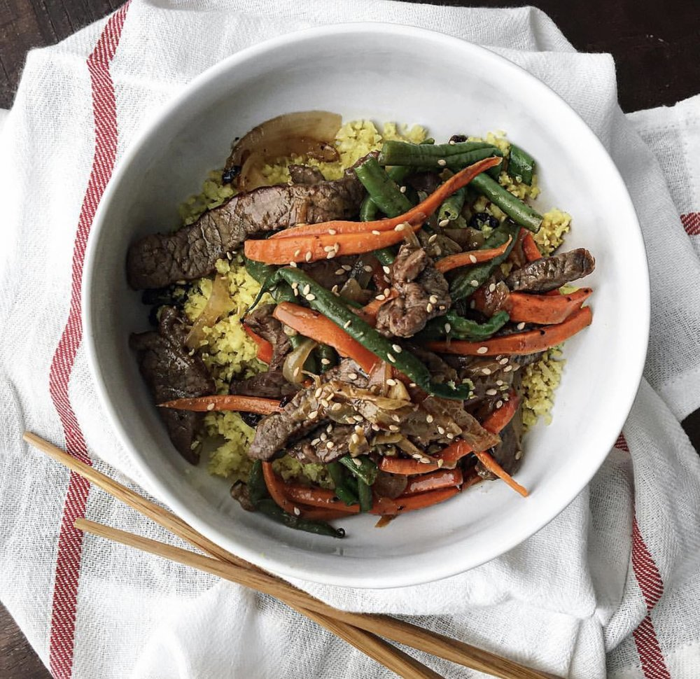 Steps:  1. Season beef w/ salt, pepper and 1/8-1/4c of coconut aminos  2. Coat beef strips with 2tbsp of arrowroot powder (will make meat more tender and moist as it cooks😊) Allow to marinate 30-60mins.  3. Stir fry beef in batches so as not to overcrowd pan till brown on all sides. Remove to a pan.  4. In the same skillet/wok add oil. Once hot, lightly sauté garlic, ginger and tangerine zest till fragrant bout 30secs . Toss in onions sauté about 2mins then add carrots and string beans for another 2-3mins. You can steam carrots and string beans first if you prefer less crunch to your veggies.  5. Return beef to pan and toss well. 6. Add tangerine juice and the remaining coconut aminos. Toss well to mix 7. Sprinkle with sesame seeds and enjoy! Serve with cauliflower rice.