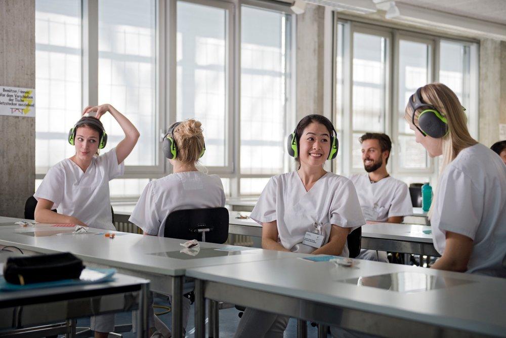 Studierende der zmk sitzen mit Gehörschützen im Vorlesungssaal und üben die Kommunikation bei Höreinschränkungen.