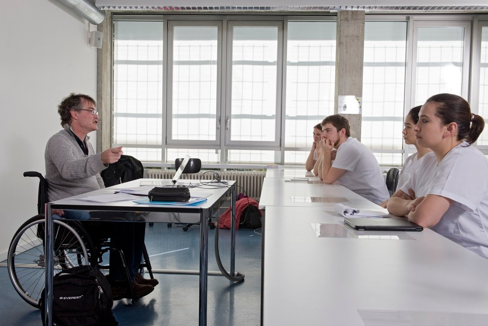 Ein Experte im Rollstuhl vermittelt den Studierenden im Hörsaal Grundlagen zur Kommunikation und Behinderung.