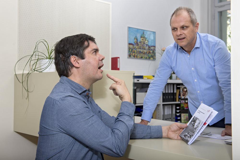 Zwei Männer am Schalter. Der Mann mit Cochlea-Implantat zeigt auf seinen Mund.