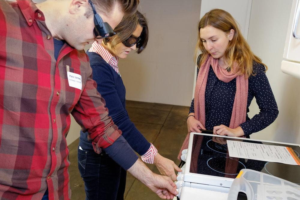 Zwei Kursteilnehmende mit Simulationsbrillen versuchen die Schalter an einem Kochherd zu bedienen. Die sehbehinderte Expertin erläutert die Schwierigkeiten.