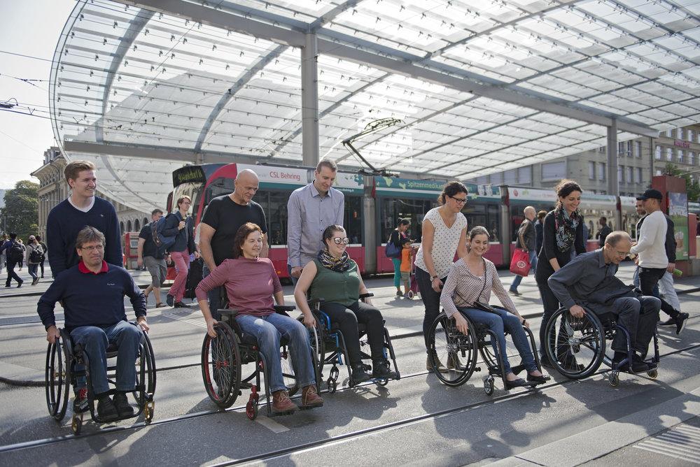 Eine Gruppe von Kursteilnehmenden im Rollstuhl und mit Begleitperson überquert Tramgeleise.