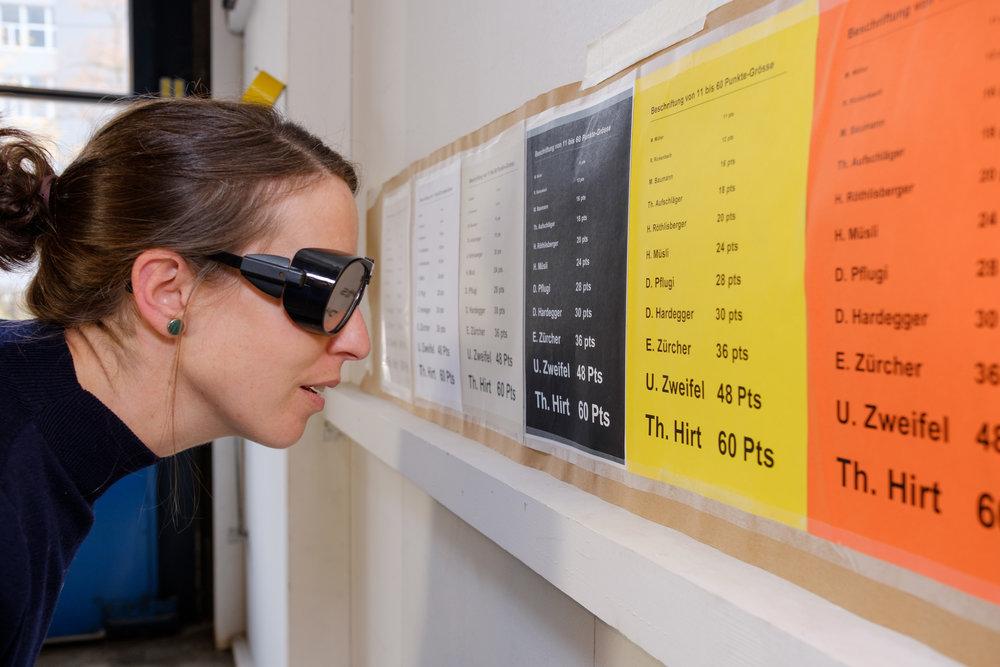 Eine Kursteilnehmerin mit Simulationsbrille beugt sich nahe zu den Schriftbeispielen an der Wand. Auf verschieden farbigen Blättern sind verschiede Schriftgrössen erkennbar.