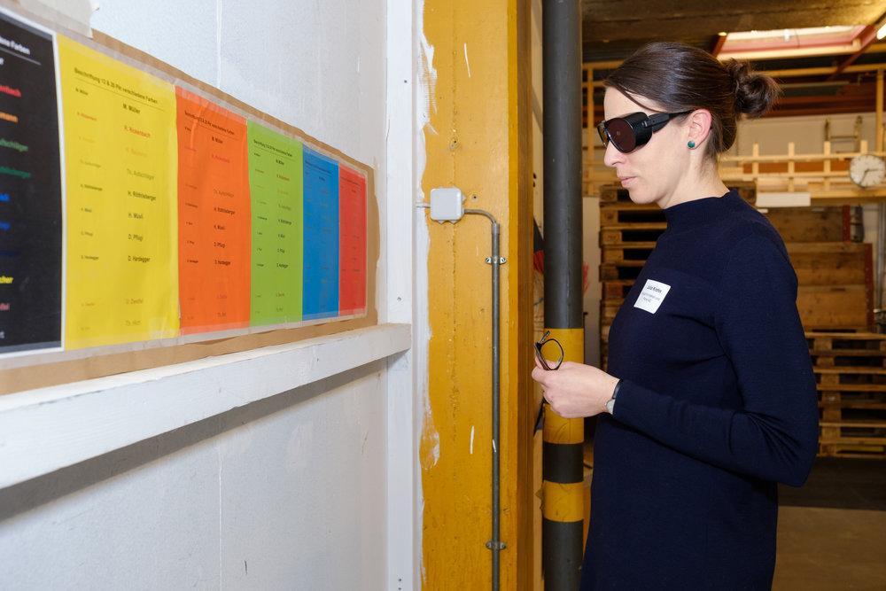 Eine Frau mit Simulationsbrille steht vor einer Wand mit verschieden farbigen Blättern. Auf diesen versucht sie Texte in verschiedenen Schriftgrössen zu lesen.