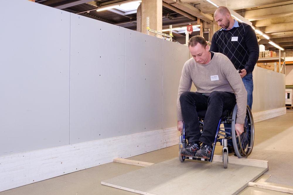 Ein Mann im Rollstuhl versucht vornübergebeugt über eine höhere Schwelle zu fahren. Dabei wird er von einem anderen Workshopteilnehmer gesichert.