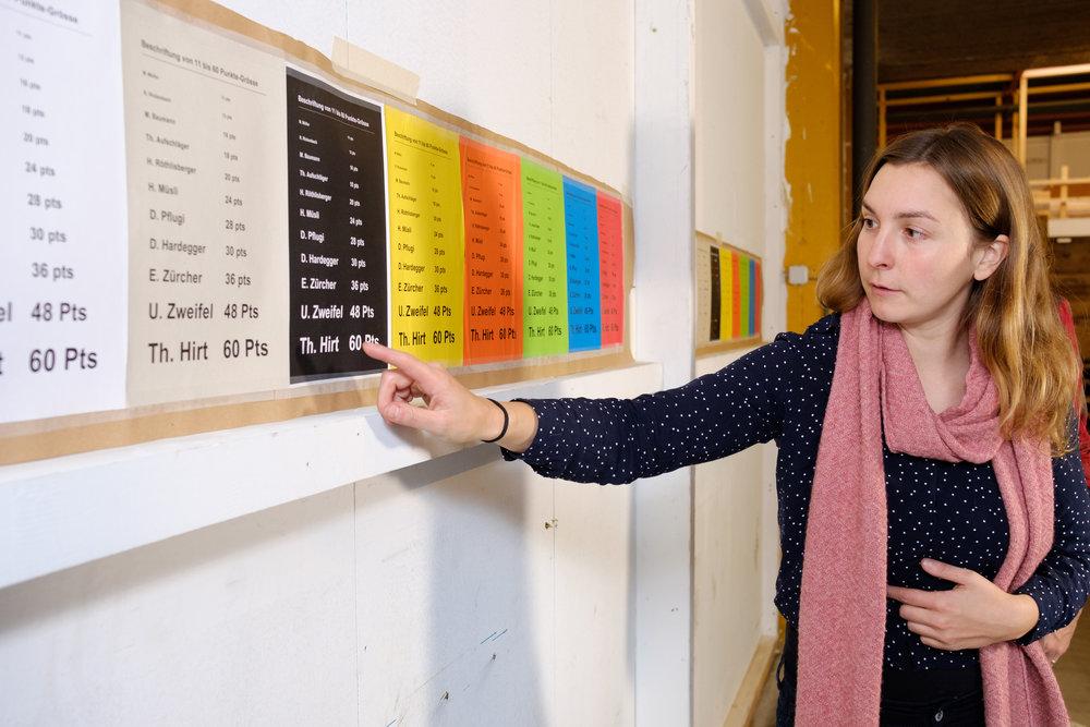 Eine sehbehinderte Kursleiterin erläutert verschiedene Schriftbeispiele, die an der Wand hängen. Sie zeigt mit einem Finger auf ein Beispiel mit weisser Schrift auf schwarzem Hintergrund.