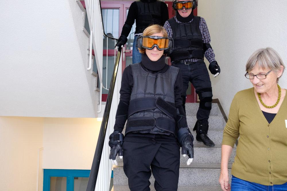 Eine Gruppe von Workshopteilnehmenden steigt im Altersanzug die Treppe hinunter.